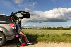 Νέα συνεδρίαση γυναικών στον κορμό ενός αυτοκινήτου, που παίρνει έτοιμο για ένα πεζοπορώ Ελεύθερο ταξίδι πίεσης Στοκ Φωτογραφίες