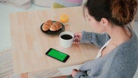 Νέα συνεδρίαση γυναικών στον πίνακα και τον καφέ κατανάλωσης στην κουζίνα Smartphone χρήσεων κοριτσιών Brunette, πράσινη οθόνη Στοκ φωτογραφία με δικαίωμα ελεύθερης χρήσης