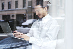 Νέα συνεδρίαση επιχειρηματιών ή σπουδαστών και εργασία στο windowsill με το ανοικτό lap-top στα γόνατα Στοκ φωτογραφίες με δικαίωμα ελεύθερης χρήσης