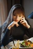 Νέα συνεδρίαση επιχειρησιακών γυναικών στον καφέ και ομιλία στο τηλέφωνο Γεύμα έννοιας Σαλάτα χυμού από πορτοκάλι και θαλασσινών Στοκ Εικόνα