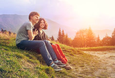 Νέα συνεδρίαση ζευγών μαζί στο ηλιοβασίλεμα στοκ φωτογραφία