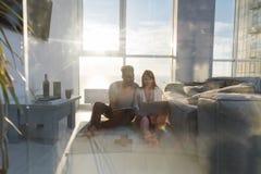 Νέα συνεδρίαση ζεύγους στο πάτωμα που χρησιμοποιεί lap-top ταμπλετών υπολογιστών τη σύγχρονη άποψη θάλασσας παραθύρων διαμερισμάτ Στοκ Φωτογραφία
