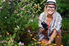 Νέα συνεδρίαση κηπουρών γυναικών κοντά στα λουλούδια στη σκαπάνη εκμετάλλευσης κήπων Στοκ εικόνες με δικαίωμα ελεύθερης χρήσης