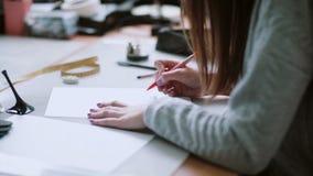 Νέα συνεδρίαση σχεδιαστών στον πίνακα και σχέδιο το σκίτσο των μπλε παπουτσιών Η γυναίκα σβήνει σε χαρτί Πλάγια όψη 4K απόθεμα βίντεο