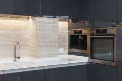 Νέα σύγχρονη κουζίνα με χτισμένος στον κρουνό φούρνων και χρωμίου Φωτισμός οδηγήσεων worktop στοκ εικόνα