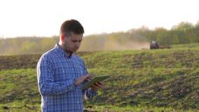 Νέα ταμπλέτα εκμετάλλευσης αγροτών μπροστά από το τρακτέρ στον τομέα Εποχιακός γεωργικός εργαζόμενος Οικολογία έννοιας, μεταφορά φιλμ μικρού μήκους