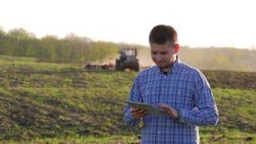 Νέα ταμπλέτα εκμετάλλευσης αγροτών μπροστά από το τρακτέρ στον τομέα Εποχιακός γεωργικός εργαζόμενος Οικολογία έννοιας, μεταφορά απόθεμα βίντεο