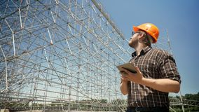 Νέα ταμπλέτα εκμετάλλευσης αρχιτεκτόνων και εξέταση την εγκατάσταση μετάλλων στο υπόβαθρο, συνοφρύωμα και σοβαρός, που προγραμματ