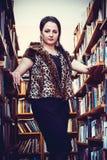 Νέα τοποθέτηση γυναικών για τη κάμερα στη βιβλιοθήκη στοκ φωτογραφία