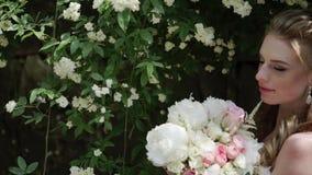 Νέα τοποθέτηση νυφών κοντά στα λουλούδια στην ηλιόλουστη ημέρα φιλμ μικρού μήκους