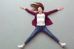 Νέα τοπ άποψη γυναικών σχετικά με το γκρι που βρίσκεται στο πάτωμα εύθυμο στοκ εικόνες