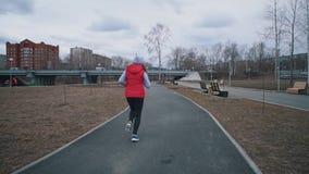 Νέα τρεξίματα γυναικών στο πάρκο τη νεφελώδη ημέρα απόθεμα βίντεο