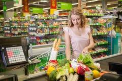 Νέα τρόφιμα αγοράς γυναικών στο παντοπωλείο στοκ φωτογραφία