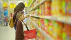 Νέα τρόφιμα αγοράς Mom και παιδιών σε μια υπεραγορά Η όμορφη γυναίκα με τη χαριτωμένη στάση κοριτσιών κοντά στο ράφι με τα αγαθά  απόθεμα βίντεο
