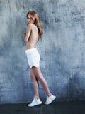 Νέα τόπλες γυναίκα στα άσπρα σορτς και τα πάνινα παπούτσια Στοκ φωτογραφία με δικαίωμα ελεύθερης χρήσης