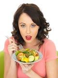 Νέα υγιής γυναίκα που κρατά ένα πιάτο της πρόσφατα μικτής σαλάτας στοκ φωτογραφία