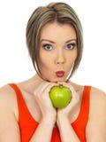 Νέα υγιής γυναίκα που κρατά τη φρέσκια ώριμη λαμπρή πράσινη Apple Στοκ Φωτογραφία
