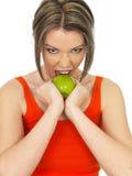 Νέα υγιής γυναίκα που κρατά τη φρέσκια ώριμη πράσινη Apple Στοκ Φωτογραφίες