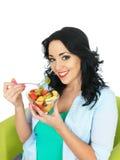 Νέα υγιής γυναίκα που τρώει μια σαλάτα νωπών καρπών Στοκ φωτογραφία με δικαίωμα ελεύθερης χρήσης