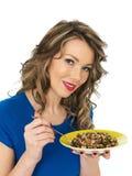Νέα υγιής γυναίκα που τρώει το άγριο ρύζι και τη μικτή σαλάτα φασολιών Στοκ Φωτογραφία