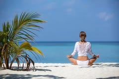 Νέα υγιής γυναίκα στην άσπρη γιόγκα άσκησης στην παραλία Μαλδίβες Στοκ Εικόνες