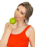 Νέα υγιής ελκυστική γυναίκα που κρατά τη φρέσκια ώριμη πράσινη Apple Στοκ εικόνες με δικαίωμα ελεύθερης χρήσης