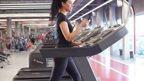 Νέα φίλαθλος που χρησιμοποιεί το smartphone jogging treadmill απόθεμα βίντεο