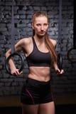 Νέα φίλαθλη γυναίκα που ασκεί με τα γυμναστικά δαχτυλίδια στη γυμναστική crossfit Στοκ φωτογραφία με δικαίωμα ελεύθερης χρήσης