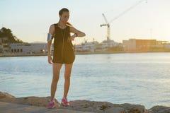 Νέα φίλαθλη προσοχή κοριτσιών στο ρολόι της στην παραλία στοκ εικόνες με δικαίωμα ελεύθερης χρήσης