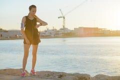 Νέα φίλαθλη προσοχή κοριτσιών στο ρολόι της στην παραλία στοκ φωτογραφία