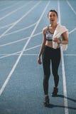 Νέα φίλαθλος με την πετσέτα που στέκεται στο τρέξιμο του σταδίου διαδρομής Στοκ φωτογραφίες με δικαίωμα ελεύθερης χρήσης