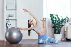 Νέα φίλαθλος που κάνει τις ασκήσεις με τη σφαίρα σε ένα χαλί στο σπίτι Στοκ εικόνα με δικαίωμα ελεύθερης χρήσης