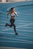 Νέα φίλαθλος που τρέχει γρήγορα στο τρέξιμο του σταδίου διαδρομής Στοκ φωτογραφία με δικαίωμα ελεύθερης χρήσης