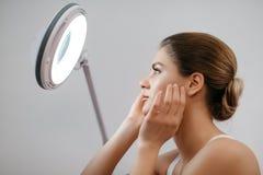 Νέα φρέσκια γυναίκα με το ξανθό updo τρίχας σχετικά με το πρόσωπό της εξετάζοντας το cocmetic λαμπτήρα στο άσπρο υπόβαθρο Στοκ εικόνα με δικαίωμα ελεύθερης χρήσης