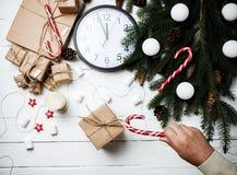 Νέα χέρια ατόμων έννοιας έτους σύνθεσης Χριστουγέννων με το γάντζο καραμελών Στοκ εικόνες με δικαίωμα ελεύθερης χρήσης