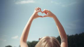 Νέα χέρια αύξησης γυναικών σε έναν ουρανό στη μορφή της καρδιάς απόθεμα βίντεο