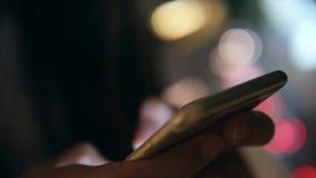 Νέα χέρια γυναικών που χρησιμοποιούν Smartphone με το θολωμένο Bokeh υπόβαθρο οδικών φω'των νύχτας οδών αστικό 4K bangkok thailan απόθεμα βίντεο