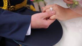 Νέα χέρια εκμετάλλευσης παντρεμένων ζευγαριών, ημέρα γάμου τελετής Κλείστε επάνω το νεόνυμφο βάζει το γαμήλιο δαχτυλίδι στη νύφη απόθεμα βίντεο
