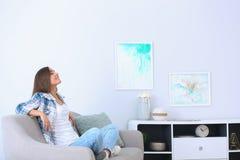 Νέα χαλάρωση γυναικών κάτω από το κλιματιστικό μηχάνημα στοκ φωτογραφίες