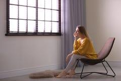 Νέα χαλάρωση γυναικών κοντά στο παράθυρο με τους τυφλούς στο σπίτι στοκ φωτογραφία με δικαίωμα ελεύθερης χρήσης