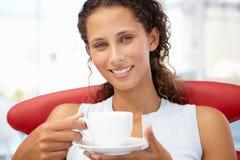 Νέα χαλάρωση γυναικών με το φλυτζάνι του τσαγιού στοκ φωτογραφία με δικαίωμα ελεύθερης χρήσης