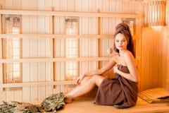 Νέα χαλάρωση γυναικών σε μια σάουνα που ντύνεται σε μια πετσέτα Εσωτερικό της νέας φινλανδικής σάουνας, υπέρυθρες επιτροπές για ι Στοκ εικόνα με δικαίωμα ελεύθερης χρήσης