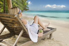 Νέα χαλάρωση γυναικών σε μια τροπική παραλία στοκ εικόνες