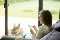 Νέα χαλάρωση γυναικών στον καναπέ που χρησιμοποιεί το smartphone apps μέσα στο σπίτι Στοκ φωτογραφίες με δικαίωμα ελεύθερης χρήσης
