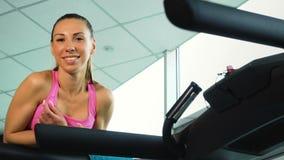 Νέα χαλάρωση γυναικών χαμόγελου treadmill στη λέσχη ικανότητας φιλμ μικρού μήκους