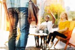 Νέα χαλάρωση ζευγών σε έναν καφέ και παρατήρηση του φίλου τους Στοκ Εικόνες