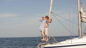 Νέα χαλάρωση ζεύγους σε ένα γιοτ Οπισθοσκόπος των χαλαρώνοντας ανθρώπων sailboat φιλμ μικρού μήκους