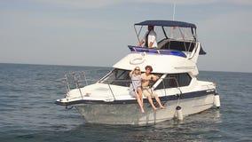 Νέα χαλάρωση ζεύγους σε ένα γιοτ Οπισθοσκόπος των χαλαρώνοντας ανθρώπων sailboat απόθεμα βίντεο