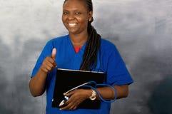 Νέα χαμογελώντας γυναίκα γιατρών με τη χειρονομία χεριών στοκ εικόνα