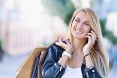 Νέα χαμογελώντας γυναίκα με η συζήτηση τσαντών με κυψελοειδές τηλέφωνο Στοκ εικόνες με δικαίωμα ελεύθερης χρήσης